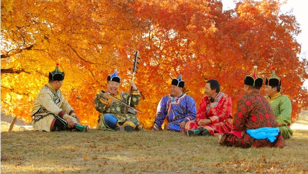An artist (L2) performs traditional musical instrument on the Horqin Grassland, Inner Mongolia autonomous region. [Photo/China SCIO]